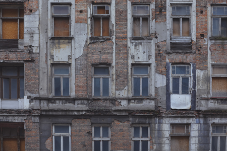 A front of the building in the center of Warsaw that is partially destroyed by nature and climate.