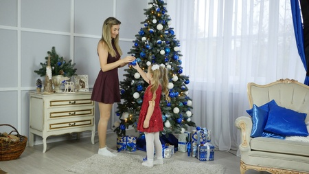 Mom and daughter decorate Christmas tree 스톡 콘텐츠