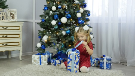 little girl with a new year gift 스톡 콘텐츠