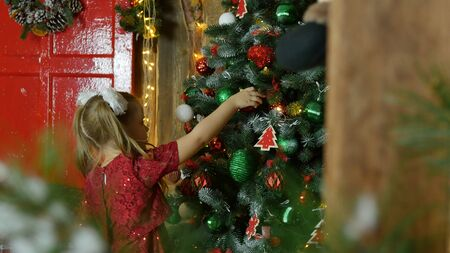 little girl hanging on the Christmas tree toys 스톡 콘텐츠