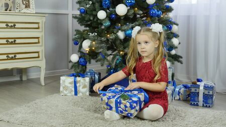 a little girl in a blue dress unpacks a New Years gift under a Christmas tree 스톡 콘텐츠