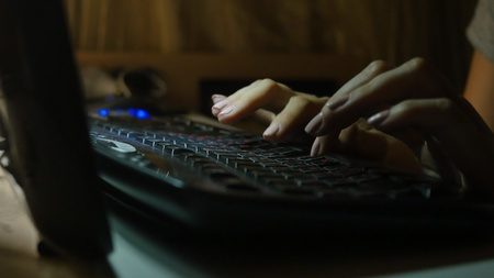 fingers typing on the keyboard at night