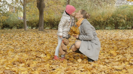 Mom and baby collect yellow fallen leaves in the park