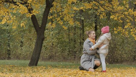 mom hugs a little daughter in the autumn forest 스톡 콘텐츠
