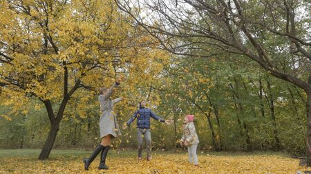 daddy turns child in autumn park. dad twirling a child on a background of yellow leaves