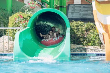 European lady and her son are enjoying their vacations. They are having fun in waterpark. They sliding down slide in waterpark.