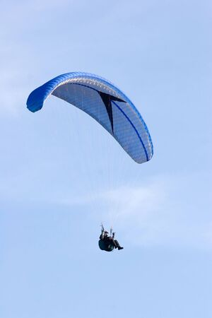 paraglinder flyes up in the sky photo
