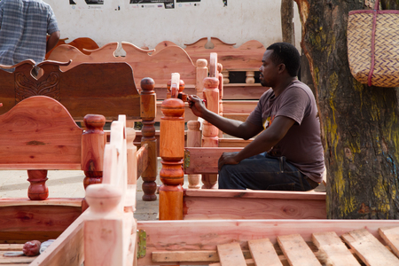 bed frame: market place, man painting a bed frame in zanzibar