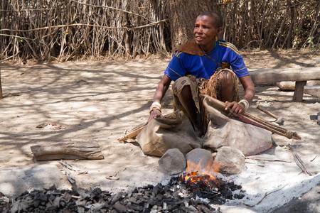hunter gatherer: datoga tribe, woman lighting a fire to forge the iron, tanzania