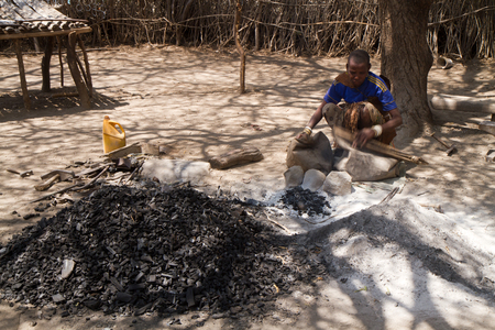 hunter gatherer: datoga woman working iron with fire in her village in tanzania