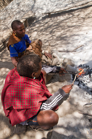 hunter gatherer: datoga family while working iron in their village in tanzania