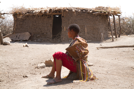 hunter gatherer: datoga woman sitting in the middle of her village