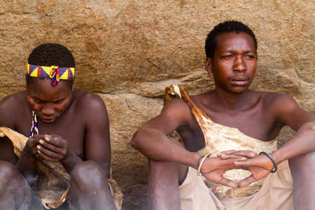 hunter gatherer: hadzabe boys sitting under rock Editorial