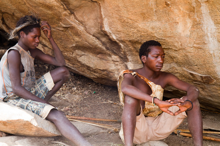 hadzabe tribe, two young men sitting in the shade of a rock