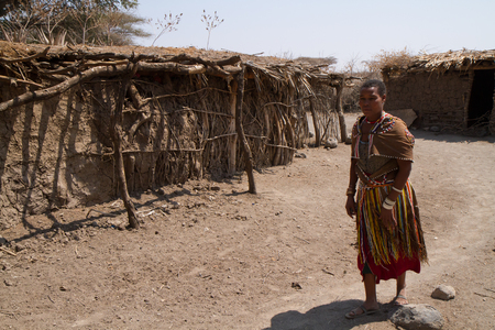 hunter gatherer: datoga tribe, woman in front of the hut, tanzania Editorial