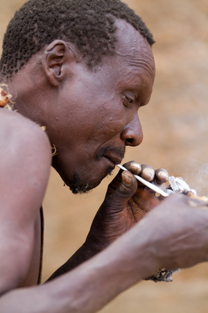 hunter gatherer: hadzabe tribe, tribesman lighting a cigarette, tanzania Editorial
