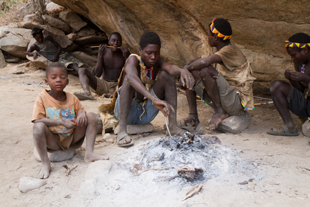 hunter gatherer: hadzabe people sitting around a fire in tanzania
