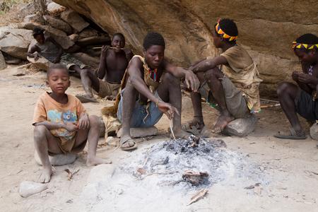 gatherer: hadzabe people sitting around a fire in tanzania