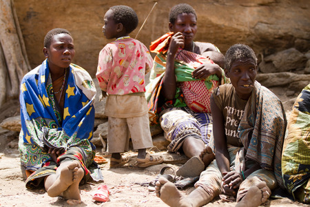 gatherer: hadzabe tribe, women sitting with their children in the village, tanzania