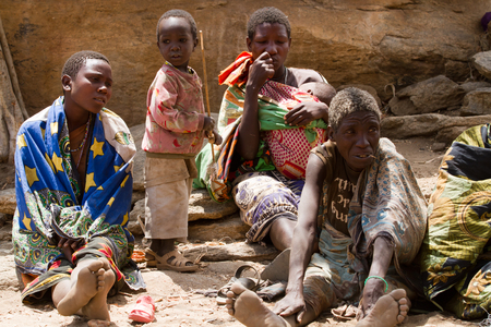 hunter gatherer: hadzabe tribe, women sitting with their children in the village, tanzania