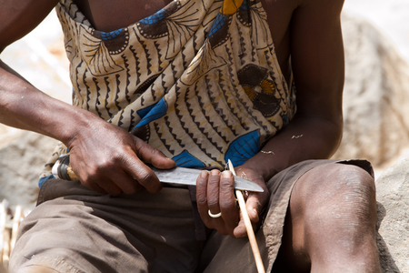 hunter gatherer: hadzabe tribe young man making the arrow to hunt, tanzania Editorial