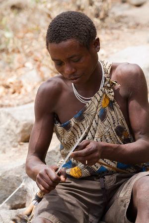 hunter gatherer: hadzabe boy making an arrow for hunting Editorial