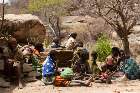 hunter gatherer: hadzabe tribe women and children sitting in the village, tanzania