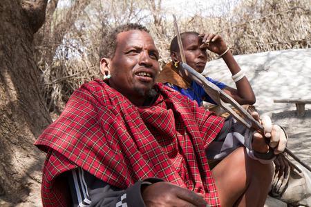 hunter gatherer: datoga family sitting in the shade of a tree in tanzania Editorial