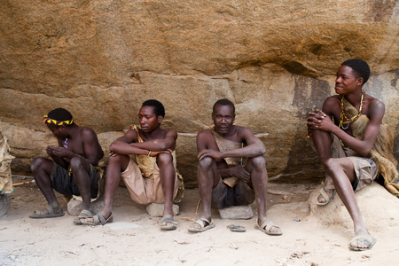 hunter gatherer: hadzabe people sitting in the shade of a rock in tanzania Editorial