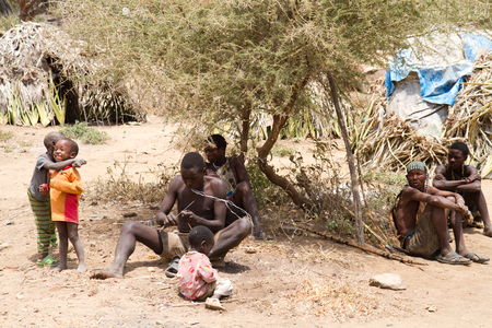 hunter gatherer: hadzabe people sitting in the shade of a tree Editorial