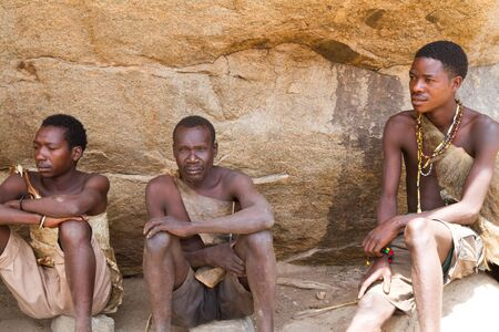hunter gatherer: hadzabe tribe young men sitting together Editorial