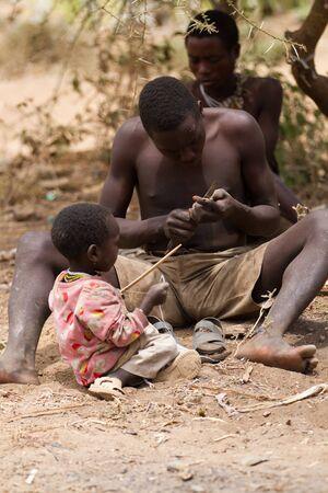 tribu: joven tribu Hadzabe haciendo una flecha