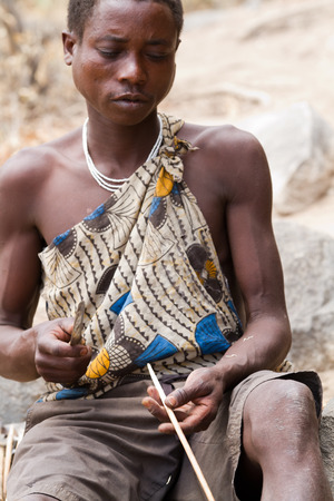 hunter gatherer: hadzabe tribe, young man making an arrow Editorial