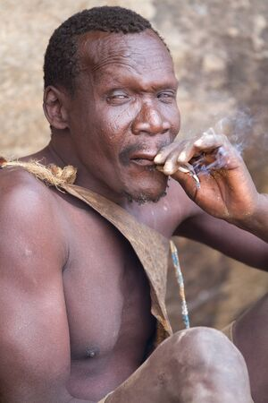 hunter gatherer: hadzabe tribe, elderly man smoking a cigarette