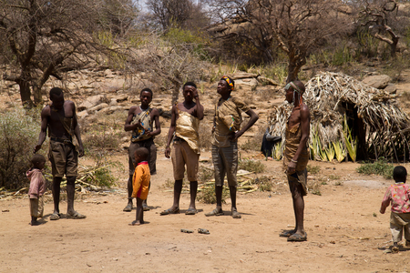 hunter gatherer: hadzabe tribe, young men standing in their village Editorial