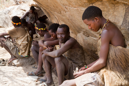 hunter gatherer: hadzabe tribe, men sitting in the shade of a rock