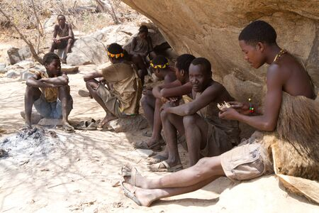 hunter gatherer: hadzabe tribe resting in the shade of the rocks