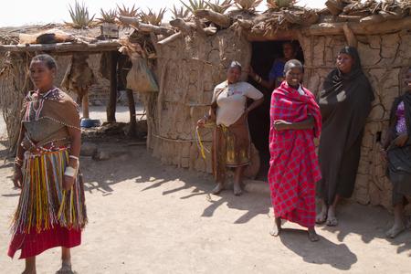 gatherer: datonga tribe woman near their hut