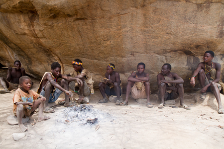 hunter gatherer: hadzabe men sitting around a fire in a village of tanzania