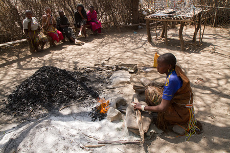 hunter gatherer: datoga tribe, woman lighting the fire to forge the iron, tanzania