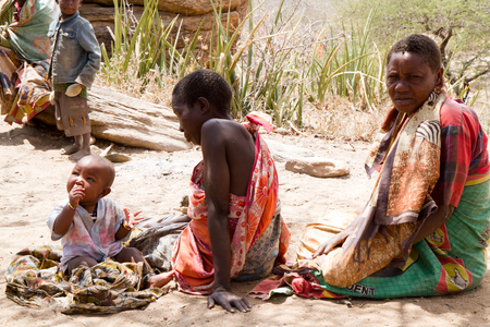 hunter gatherer: hadzabe tribe women with children in the village, tanzania Editorial