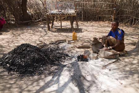 hunter gatherer: datoga tribe woman lighting the fire, tanzania
