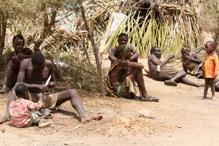 hunter gatherer: hadzabe people under a tree of their village