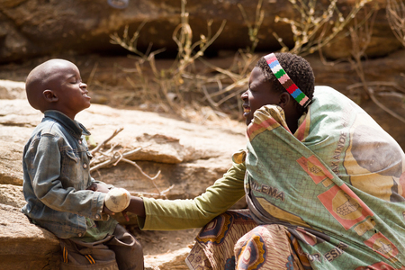 hunter gatherer: hadzabe tribe woman playing with her child