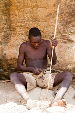 hunter gatherer: hadzabe man making an arrow used to hunt Editorial