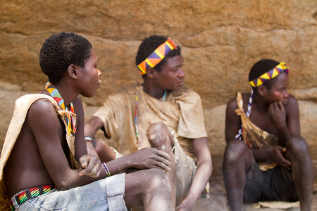 hunter gatherer: hadzabe men sitting together in the shade Editorial