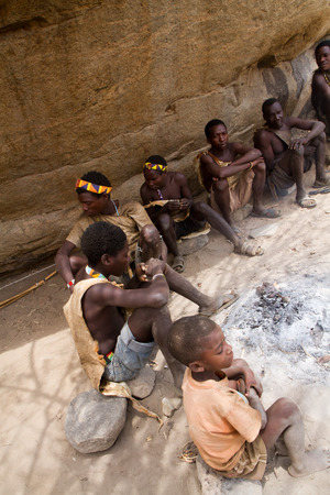 hunter gatherer: hadzabe people around a fire in tanzania