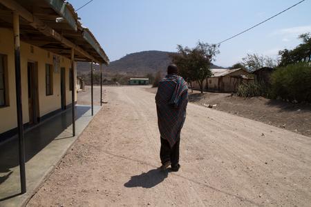 hunter gatherer: man walking on a dusty road of Tanzania