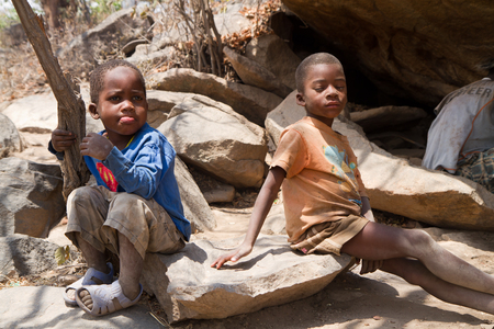 hunter gatherer: hadzabe children sitting on a stone in a village of tanzania