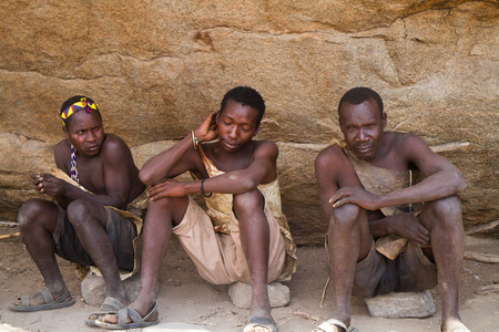 hunter gatherer: hadzabe men sitting in the shade in tanzania